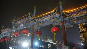 拥挤步行在唐人街,中国北京夜市场、纪念曲拱&灯笼 股票视频