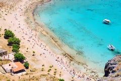拥挤海滩的顶视图与白色沙子和绿松石海的 游人的一个普遍的避风港 图库摄影