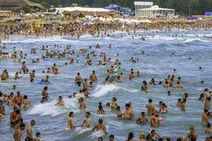 拥挤海滩和人在海挥动 库存照片