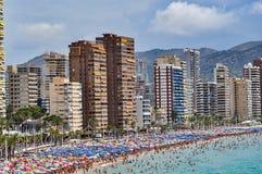 拥挤海滩贝尼多姆在一多云天 免版税图库摄影