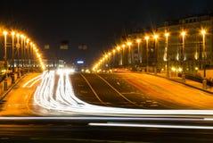 拥挤的街在城市在晚上,有很多汽车轻的条纹动态夜射击了与长的曝光 库存照片