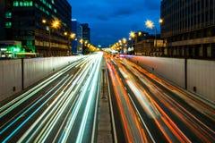 拥挤的街在黄昏的城市,有很多汽车轻的条纹动态蓝色小时射击了与长的曝光 免版税库存图片