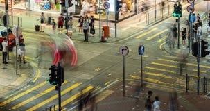 拥挤的街旺角的交叉点和步行者时间间隔有交通的在晚上在香港 股票录像