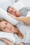 阻拦她的从丈夫噪声的疲乏的妻子耳朵打鼾看照相机 免版税库存图片