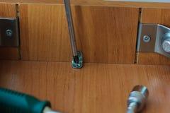 拧紧螺丝的手对与螺丝刀的一把木椅子 库存照片