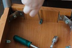 拧紧螺丝的手对与螺丝刀的一把木椅子 免版税库存照片