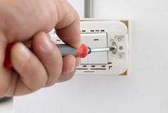 拧紧电源开关的Electrictian在房子里 免版税库存图片