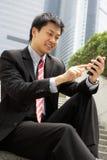 拨号在移动电话的中国生意人 库存照片