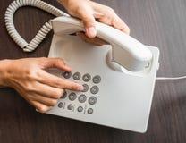 拨号在键盘的一个电话的女性手 免版税库存图片