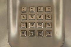 拨号盘在使用的公用电话的数字按钮 免版税库存照片