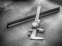 拨号盘轮尺和统治者在金工车间钢长凳 免版税库存照片