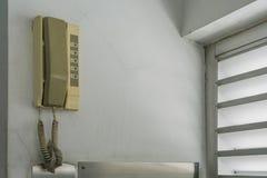 拨垂悬在墙壁上的紧急模式电话在电梯 免版税库存图片