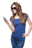拨她的手机的太阳镜的妇女 库存照片