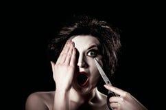 拨开她的眼睛的美丽的少妇与剪刀 免版税库存照片