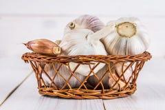 拨蒜和大蒜电灯泡在一个篮子在一白色木tabl 免版税库存照片