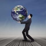 拯救世界的年轻商人尝试 免版税库存照片