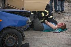 拯救出血妇女的消防队员从中一辆被碰撞的汽车 库存图片