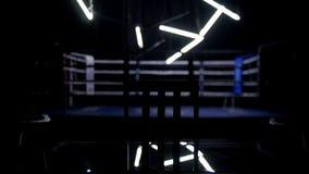 拳击台和两把椅子有桌黑暗背景 蓝色围拢的一座规则拳击台的看法系住spotlit  库存图片