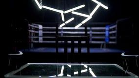 拳击台和两把椅子有桌黑暗背景 蓝色围拢的一座规则拳击台的看法系住spotlit  免版税库存照片