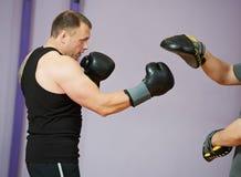 拳击培训的拳击手人与打孔机露指手套 免版税库存照片