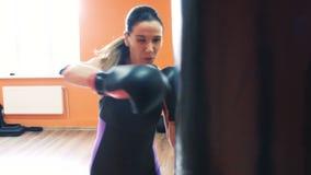 拳击手套的亭亭玉立的女孩打在健身房的吊袋与个人教练 与辅导员的锻炼健身房锻炼的 影视素材