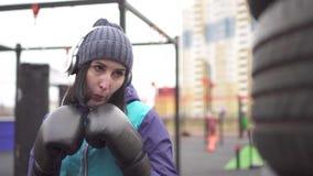 拳击手套的女子运动员搅拌在街道训练场,关闭的一个梨  股票录像