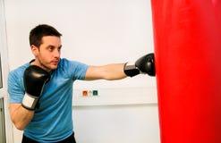 拳击手训练行使与一个沙袋在健身房 库存照片