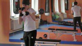 拳击的在健身房,在哑铃的教练一名精力充沛的妇女 股票录像