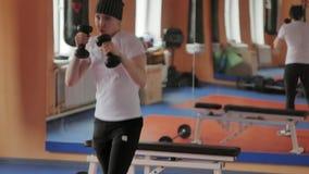 拳击的在健身房,在哑铃的教练一名精力充沛的妇女 股票视频