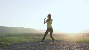 拳击` s女孩做锻炼的在山顶部在日落或日出她行使高起动自然 女性 股票视频