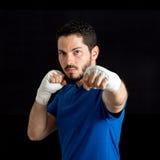 给拳打的用左手的人 黑背景,有选择性的focu 库存照片