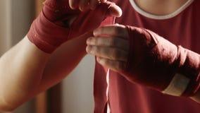 年轻拳击手拉扯在手上的红色绷带 影视素材