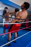 年轻拳击手猛击的男性竞争者 免版税库存照片
