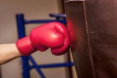 拳击手的特写镜头手在冲击的时刻对沙袋 库存图片