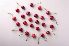 拷贝樱桃莓果空间圈子与词根的在木白色背景和水下落顶视图 免版税库存图片
