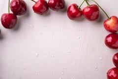 拷贝空间与词根的樱桃莓果在木白色背景和水下落顶视图 免版税库存照片