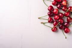 拷贝空间与词根的樱桃莓果在木白色背景和水下落顶视图 免版税库存图片