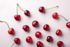 拷贝空间与词根的樱桃莓果在木白色背景和水下落顶视图 免版税图库摄影