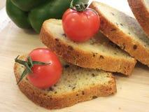 拼写沙粒面包切片、油麻和新鲜蔬菜 图库摄影