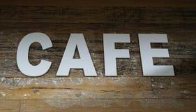 拼写词咖啡馆的白色信件计划在年迈的木背景 库存照片