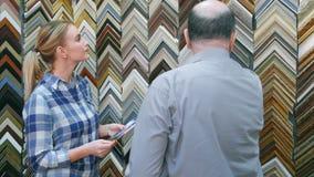 拾起一张图片的年轻女性客户一个框架在资深卖主帮助下  免版税库存图片