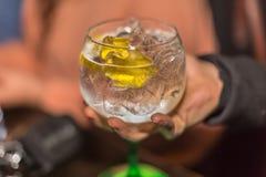 拾起一杯刷新的杜松子酒的手看法,用柠檬和许多冰,经典玻璃 库存图片