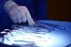 拾起仪器的外科医生手 免版税库存图片