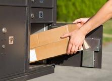 拾起在邮箱的包裹 免版税库存照片