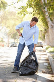 拾起在郊区街道的人废弃物 免版税库存图片