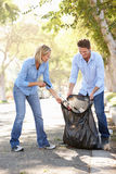 拾起在郊区街道的夫妇废弃物 免版税图库摄影
