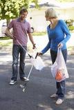拾起在郊区街道的夫妇废弃物 免版税库存照片