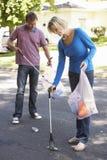拾起在郊区街道的夫妇废弃物 免版税库存图片