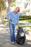 拾起在郊区街道的妇女废弃物 免版税图库摄影
