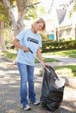 拾起在郊区街道的妇女废弃物 免版税库存图片